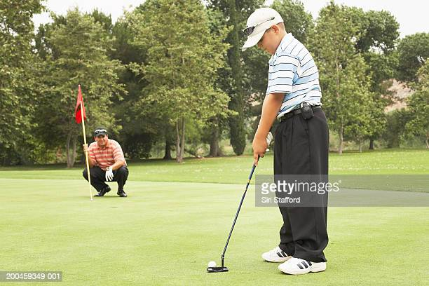 Father and son (8-10) playing golf, boy putting