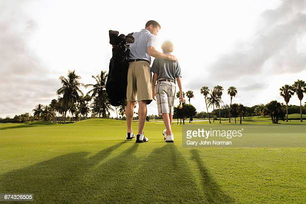 Father and son playing golf in early morning light
