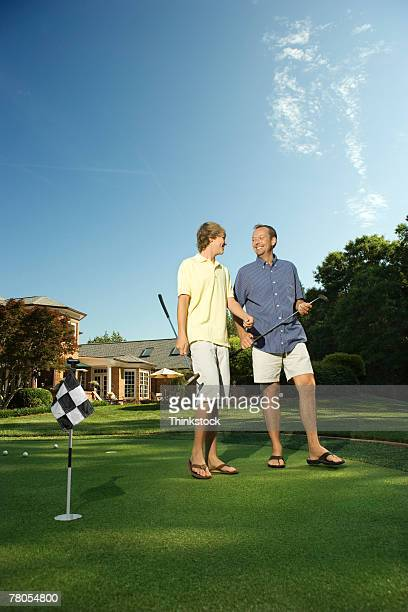 Father and son playing golf on backyard green
