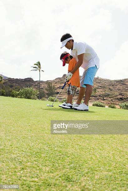 Father and son (6-7) playing golf