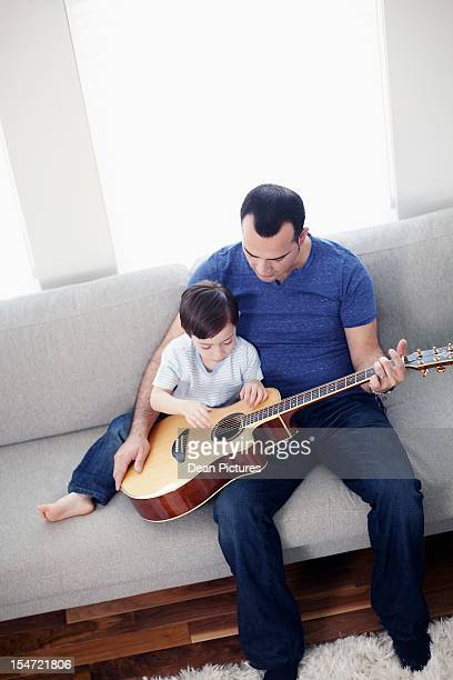 father and son (6-7) playing guitar while sitting on sofa - imagenes gratis fotografías e imágenes de stock