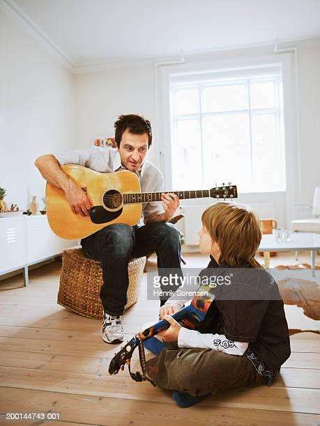 father and son (9-11) playing guitars - pizzicare le corde di uno strumento foto e immagini stock