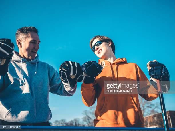 father and son playing hockey outdoors - ice hockey glove stock pictures, royalty-free photos & images