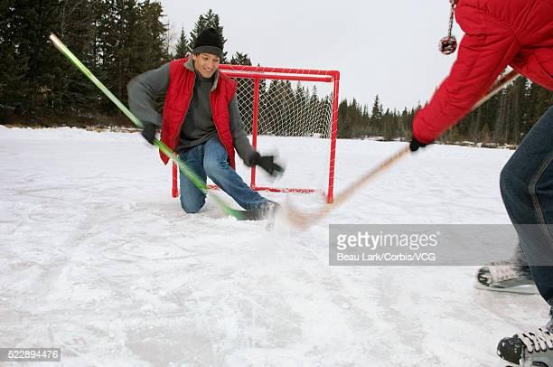 father and son playing hockey - アイスホッケーグローブ ストックフォトと画像
