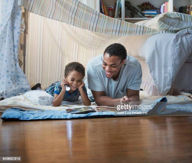 Father and son playing in blanket fort