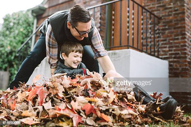father and son playing in fall leaves - rake stock pictures, royalty-free photos & images
