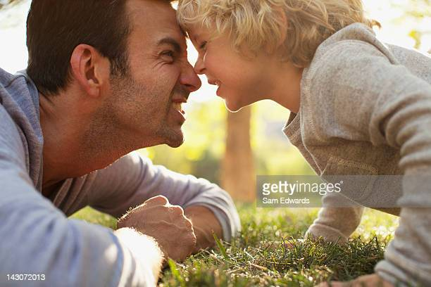 father and son playing in grass - grimacing stock pictures, royalty-free photos & images