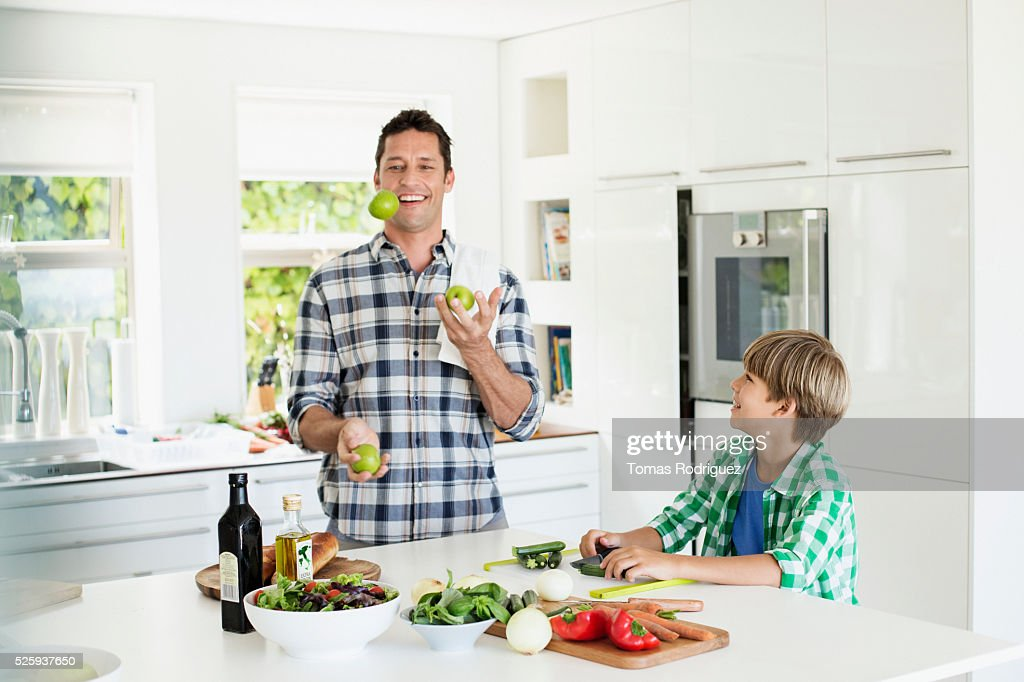 Father and son (6-7) playing in kitchen : Stock Photo