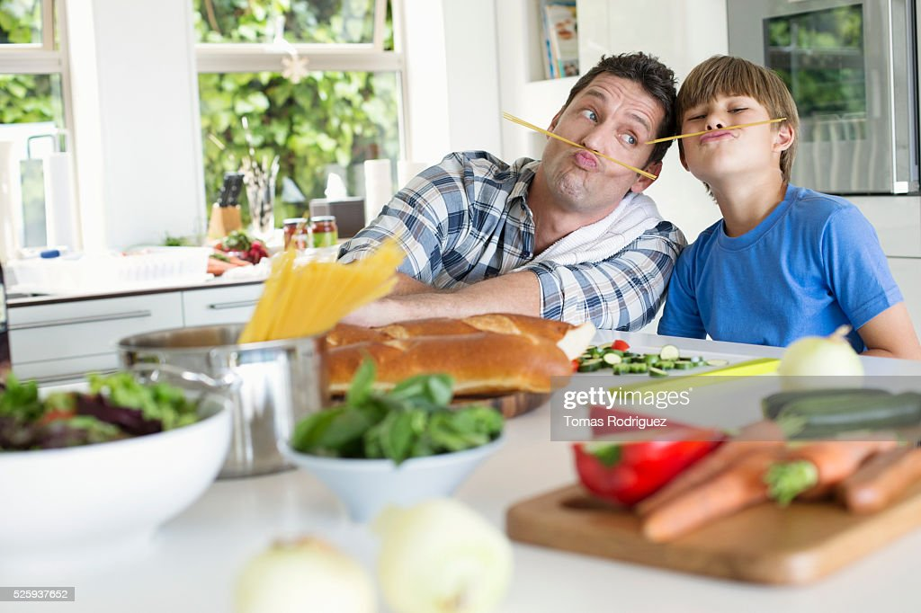 Father and son (6-7) playing in kitchen : Foto stock
