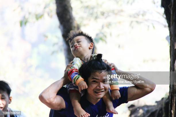 father and son playing in park - ko ko htike aung stock pictures, royalty-free photos & images