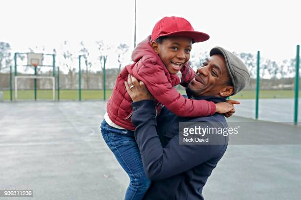 father and son (4-5) playing in park - father stock pictures, royalty-free photos & images