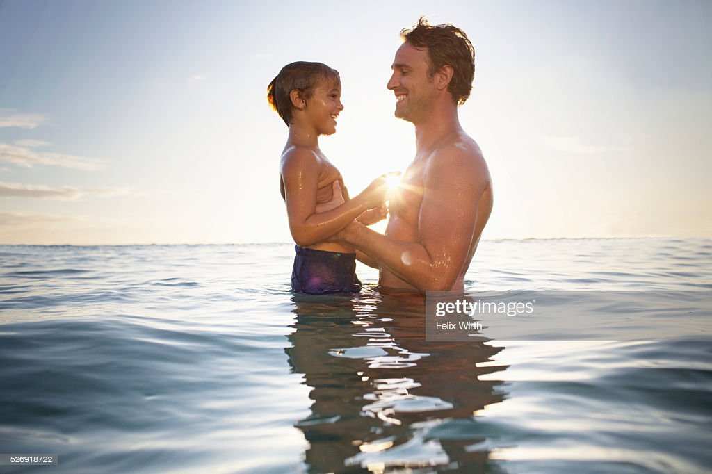 Father and son (6-7) playing in sea : Stock Photo