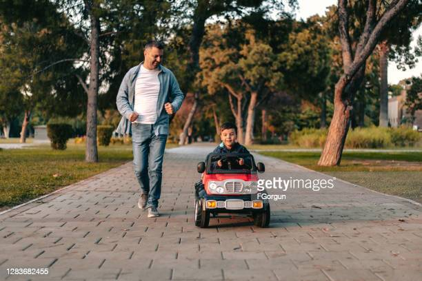 father and son playing in the park - toy car stock pictures, royalty-free photos & images