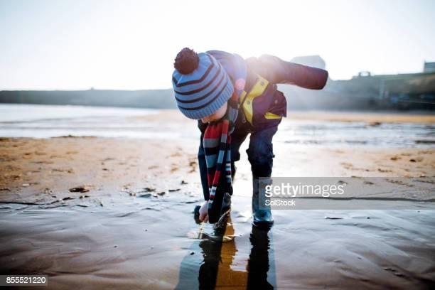 Vater und Sohn spielen im Sand an einem Wintertag