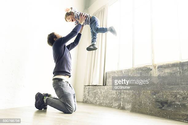 father and son playing in their apartment - wide stock pictures, royalty-free photos & images