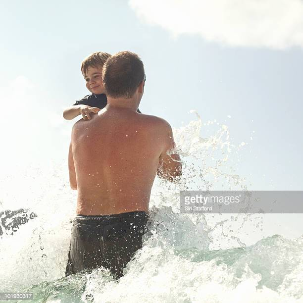 Father and son playing in waves of ocean