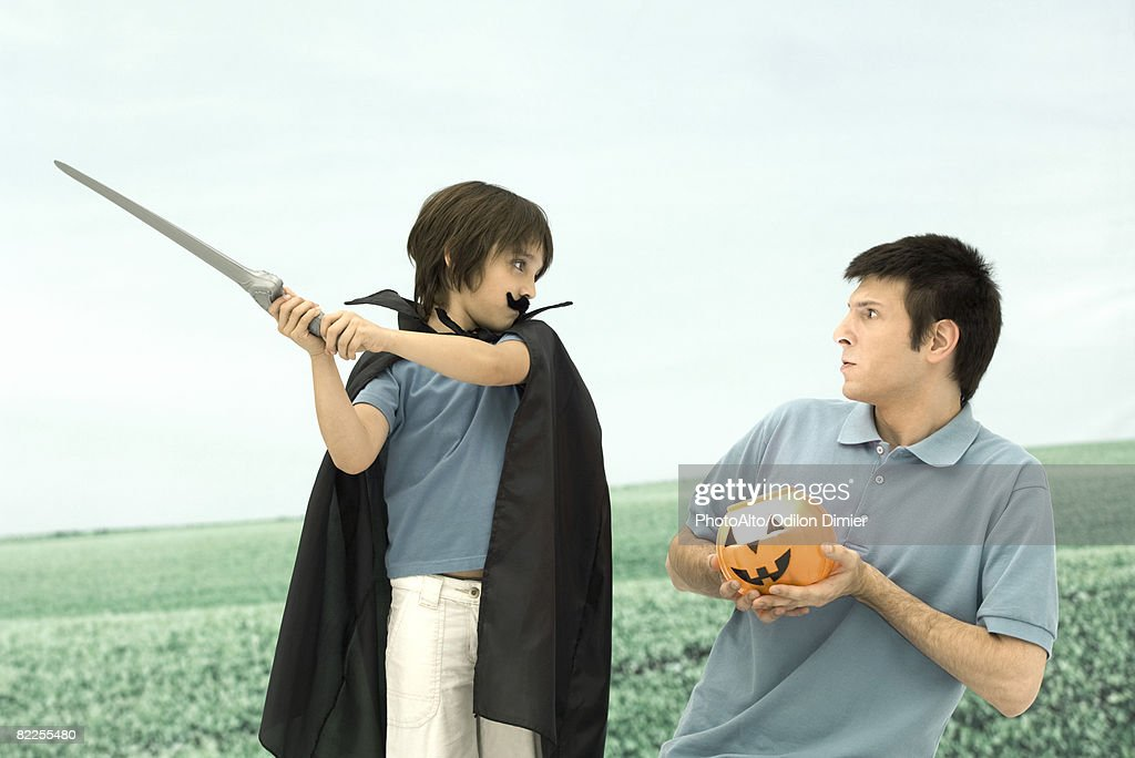 Father and son playing, man holding jack o' lantern, boy swinging sword : Stock Photo