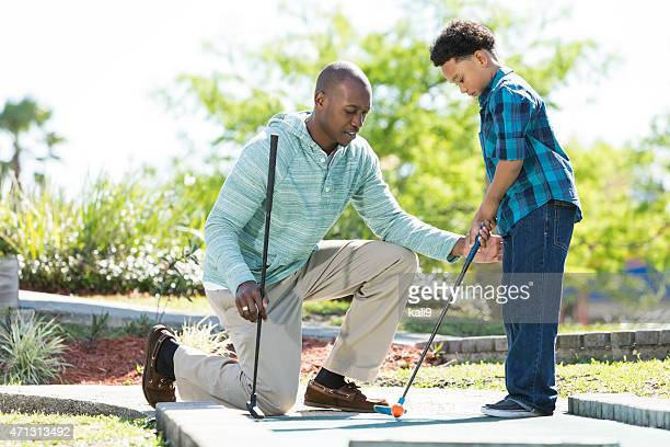 father and son playing miniature golf - miniature golf stock photos and pictures