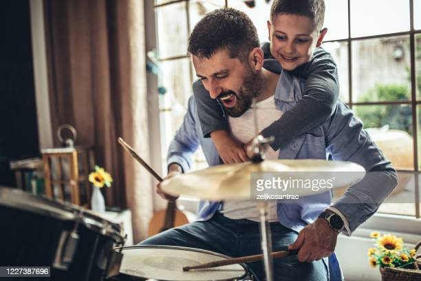 father and son playing musical instruments at home - musician stock pictures, royalty-free photos & images