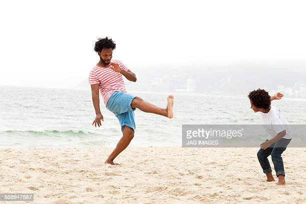 Father and son playing on beach, Riot de Janeiro, Brazil