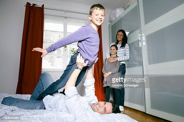 Vater und Sohn spielen auf Bett