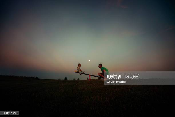 father and son playing on seesaw against sky at dusk - seesaw stock pictures, royalty-free photos & images