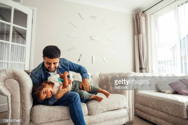 father and son playing on sofa in living room - stay at home father stock pictures, royalty-free photos & images