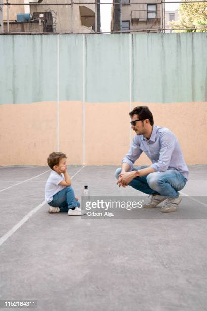 Father and son playing on tennis court