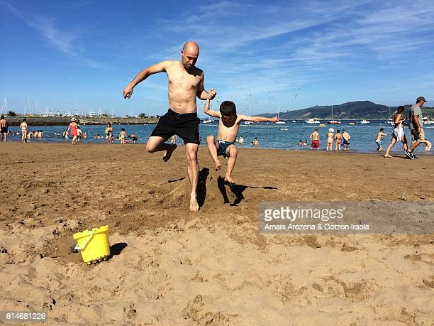 Father and son playing on the beach. Getaria, Gipuzkoa province, Basque Country