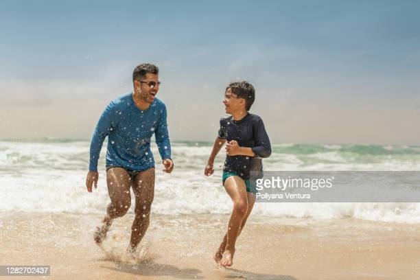 father and son playing on the beach - uv protection stock pictures, royalty-free photos & images