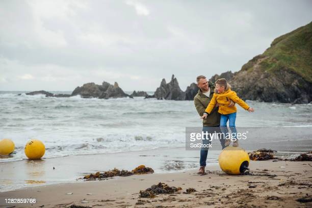 father and son playing on the beach - rain stock pictures, royalty-free photos & images