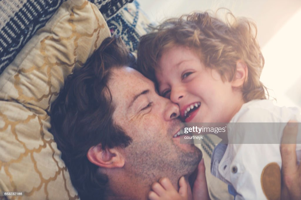 Father and son playing on the sofa. : Stock Photo