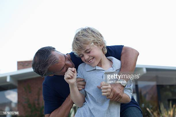 father and son playing outdoors - rough housing stock photos and pictures