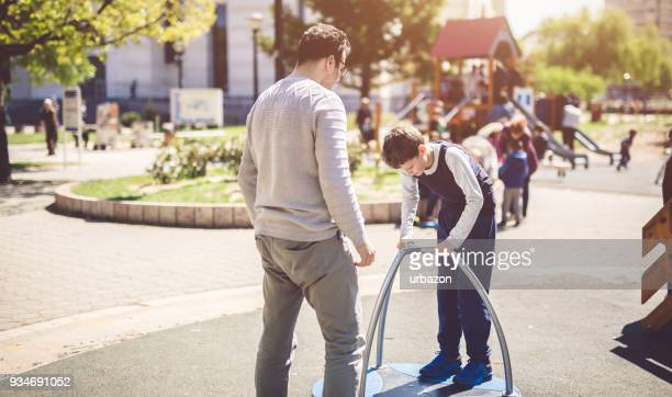 father and son playing outdoors - autism awareness stock pictures, royalty-free photos & images