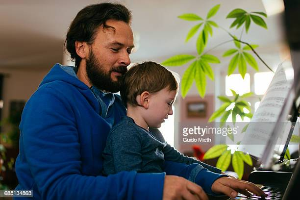 Father and son playing piano.