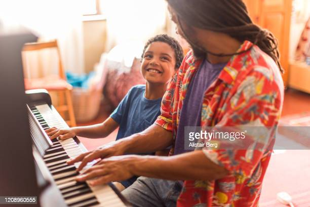 father and son playing piano together - vida simples - fotografias e filmes do acervo