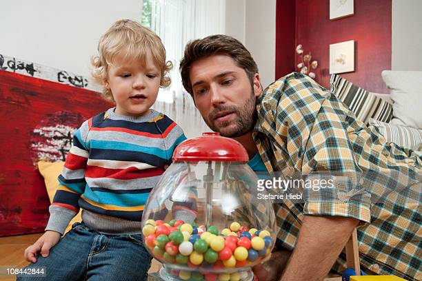 father and son playing - gumball machine stock pictures, royalty-free photos & images