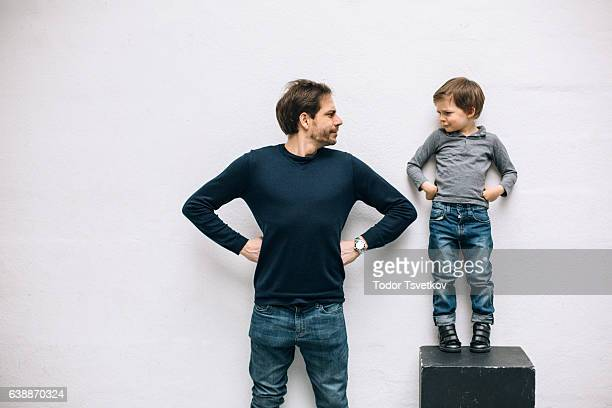 father and son playing - handen op de heupen stockfoto's en -beelden
