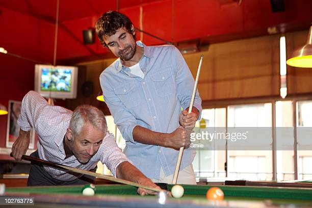 Father and son playing pool, father shooting