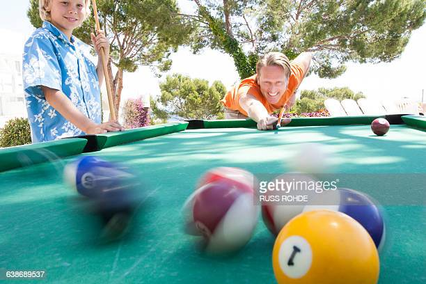 Father and son playing pool outdoors