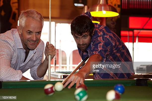 Father and son playing pool, son shooting