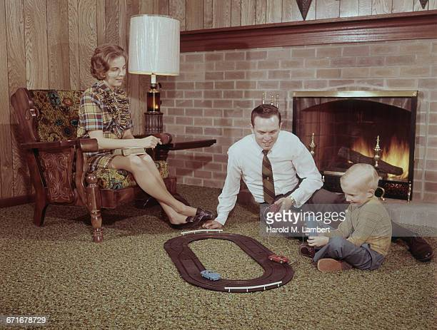 Father And Son Playing Remote Car While Mother Looking At Him