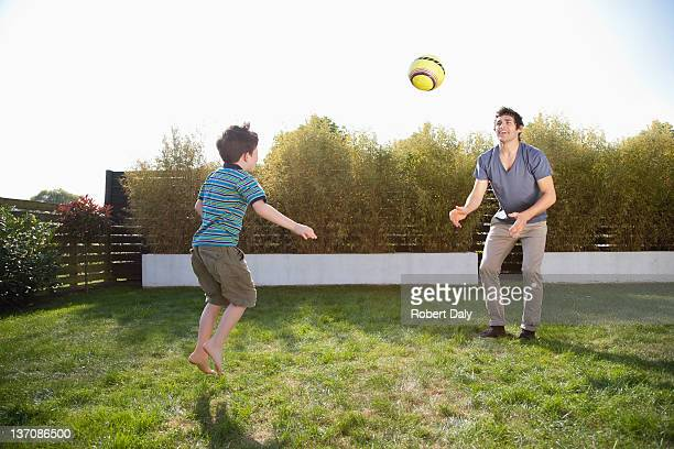 Father and son playing soccer in backyard