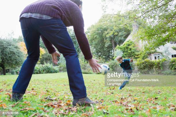 father and son playing soccer in backyard - football bulge stock photos and pictures