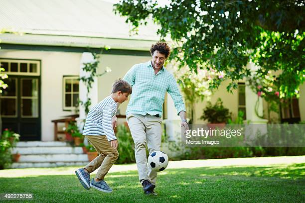 father and son playing soccer in lawn - sports ball stock pictures, royalty-free photos & images