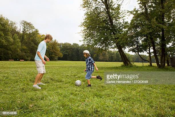 Father and son playing soccer in park, Munich, Bavaria, Germany