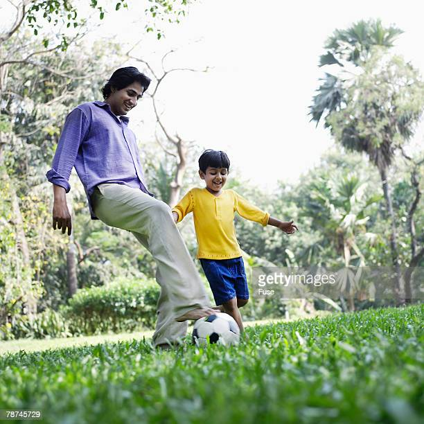 Father and Son Playing Soccer in Park
