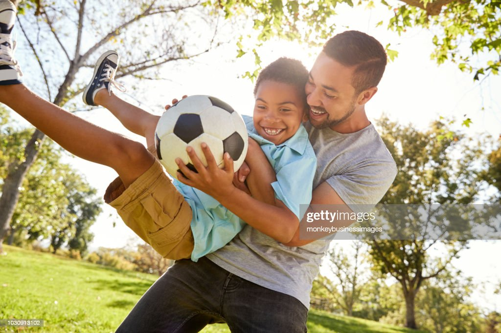 Father And Son Playing Soccer In Park Together : Stock Photo