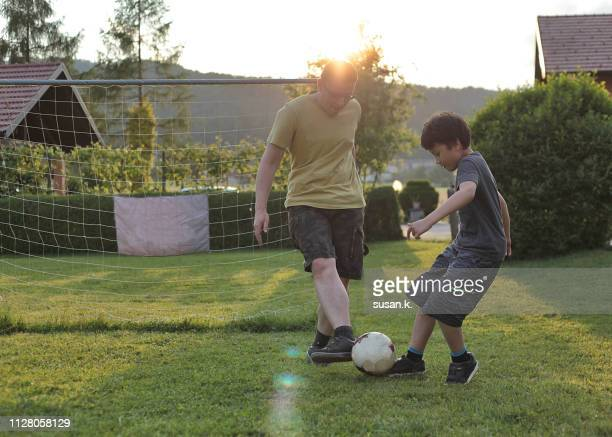 Father and son playing soccer in the backyard.