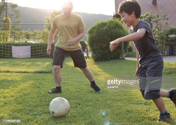 father and son playing soccer in the backyard. - team sport stock pictures, royalty-free photos & images